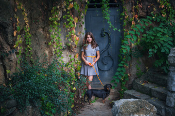 teen girl in dress with dachshund dog against  old metal door with  colorful  creeper plants around