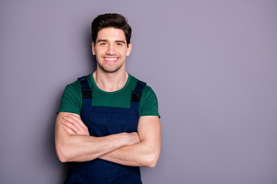Photo of handsome virile muscles guy hold arms crossed self-confident best manual worker skilled engineer wear green t-shirt blue safety dungarees isolated grey background