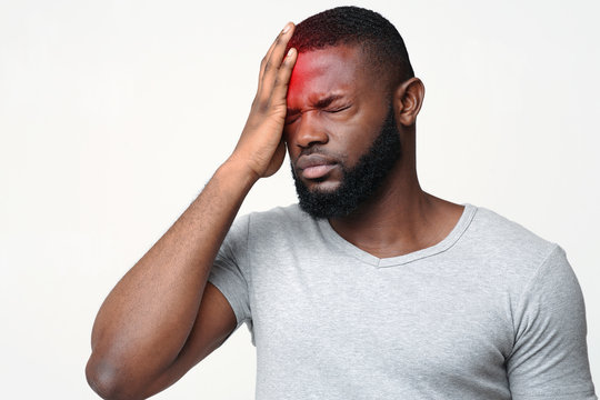 Young man suffering from terrible strong head pain