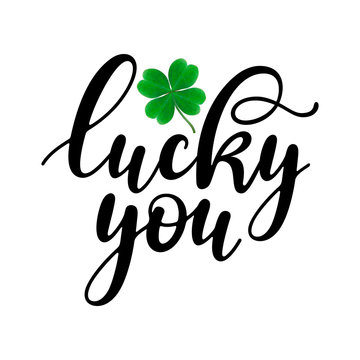 Lucky you - black handwritten lettering with four-leaf shamrock isolated on white background. 17 March St. Patrick's, Valentine's Day artwork. Good for greeting cards, t-shirt, and mug design.