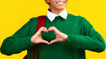 Cropped image of afro woman showing heart gesture