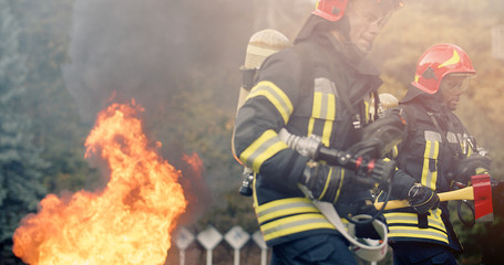 Two firefighters in fire fighting operation, fireman in protective clothing and helmet with...