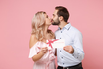 Young couple two guy girl in party outfit celebrating posing isolated on pastel pink background. People lifestyle Valentine's Day, Women's Day birthday holiday concept. Hold gift certificate, kissing.