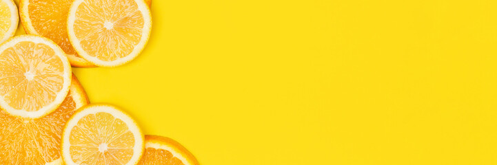 Juicy citrus on a yellow background. Bright vitamin photo. Copy space, web-banner format.