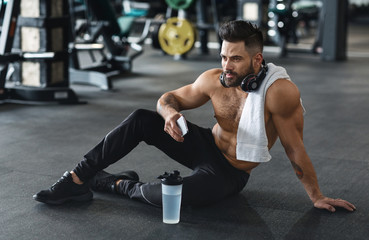 Wall Mural - Handsome hot guy resting at gym with phone and water