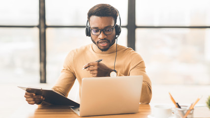 Concentrated african american guy in headset writing notes