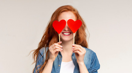 Happy redhead girl covering her eyes with red paper hearts