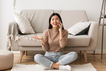 Overjoyed asian girl talking on cellphone with friend