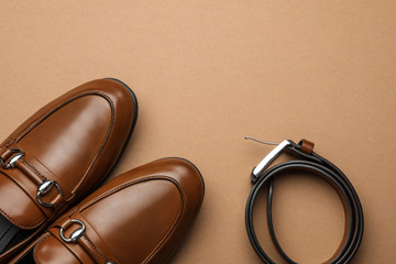 Wall Mural - Pair of stylish male shoes and leather belt on brown background, flat lay