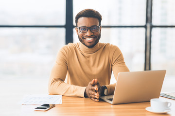Smiling black businessman working at modern office