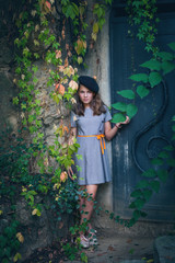 cute teen girl in dress and black beret retro style look outdoor near old metal door and colorful creeper around