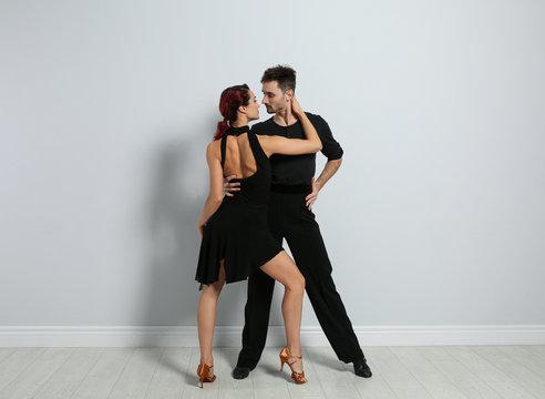 Beautiful young couple dancing near light wall