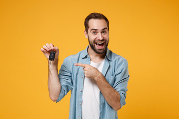 Excited young man in casual blue shirt posing isolated on yellow orange background, studio...