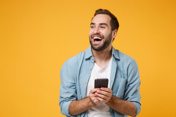 Laughing young man in casual blue shirt posing isolated on yellow orange wall background studio portrait. People emotions lifestyle concept. Mock up copy space. Using mobile phone, typing sms message.