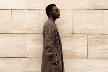 Wall Mural - Side view profile stylish african man model wearing brown knitted cardigan, sunglasses on city street over brick wall background