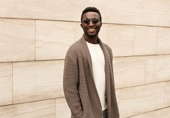 Wall Mural - Stylish smiling african man wearing brown knitted cardigan and sunglasses on city street over brick wall background
