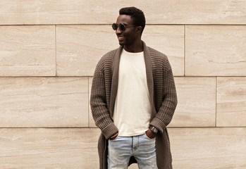 Wall Mural - Stylish smiling african man looking away wearing brown knitted cardigan and sunglasses on city street over brick wall background