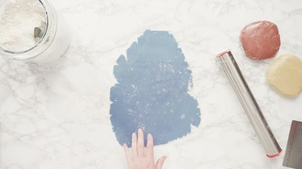 Wall Mural - Step by step. Flat lay. Rolling out dough with a rolling pin to bake red, white, and blue pinwheel sugar cookies.