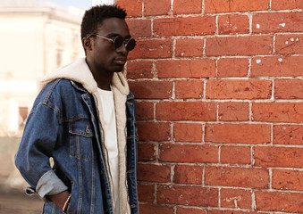 Wall Mural - Portrait side view profile stylish african man wearing jeans jacket on city street over brick textured wall background