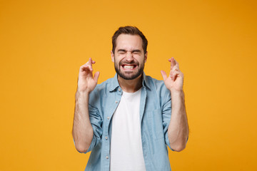 Young bearded man in blue shirt posing isolated on yellow orange background. People lifestyle concept. Mock up copy space. Waiting for special moment keeping fingers crossed, eyes closed, making wish.