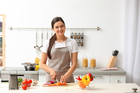 Young woman cutting vegetables for soup at table in kitchen
