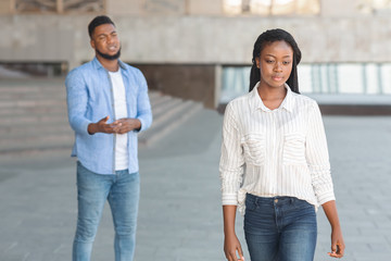 Sad black guy looking at his leaving girlfriend after arguing outdoors