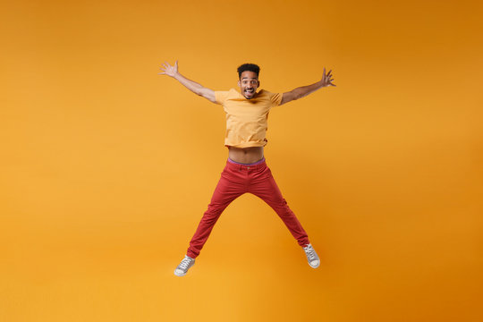 Funny young african american guy in bright casual clothes posing isolated on yellow orange background studio portrait. People lifestyle concept. Mock up copy space. Jumping spreading hands and legs.