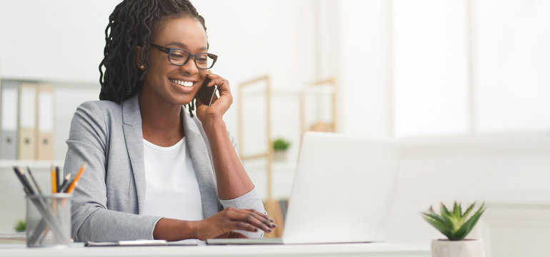 Black Businesswoman Talking On Cellphone And Using Laptop In Office, Panorama