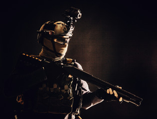 Shoulder portrait of army elite troops soldier, anti-terrorist tactical team wit shotgun, helmet with thermal imager, hiding face behind mask, armed rifle with optical scope, studio shoot on black