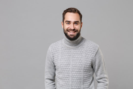 Smiling young bearded man in gray sweater posing isolated on grey wall background, studio portrait. Healthy fashion lifestyle, people emotions cold season concept. Mock up copy space. Looking camera.