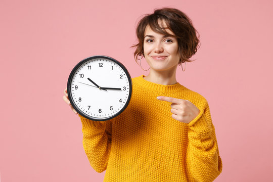 Smiling young brunette woman girl in yellow sweater posing isolated on pastel pink background in studio. People sincere emotions lifestyle concept. Mock up copy space. Pointing index finger on clock.