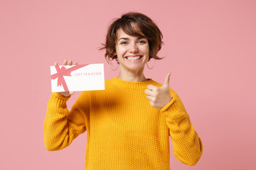 Smiling young brunette woman girl in yellow sweater posing isolated on pastel pink background...