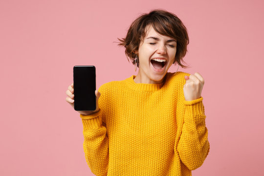 Happy young brunette woman in yellow sweater posing isolated on pastel pink background. People lifestyle concept. Mock up copy space. Hold mobile phone with blank empty screen, doing winner gesture.