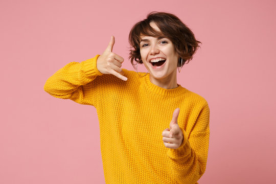 Young brunette woman girl in yellow sweater posing isolated on pink background. People lifestyle concept. Mock up copy space. Doing phone gesture like says call me back, point index finger on camera.