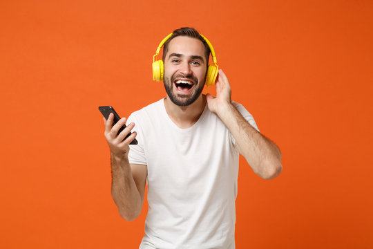 Laughing young man in casual white t-shirt posing isolated on orange wall background studio portrait. People lifestyle concept. Mock up copy space. Listening music with headphones, hold mobile phone.