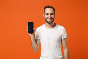 Smiling young man in casual white t-shirt posing isolated on bright orange wall background, studio...
