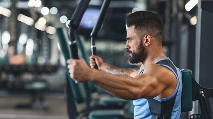 Wall Mural - Young bodybuilder exercising on training apparatus at gym