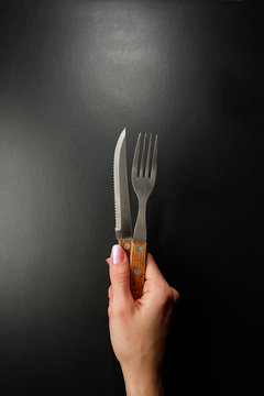 Knife and fork with a wooden handle in a female hand. Black background