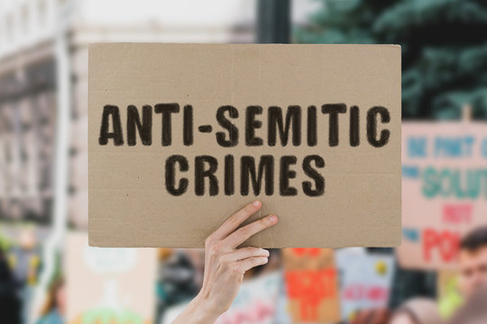 "The phrase "" Anti-Semitic crimes "" on a banner in men's hand. Human holds a cardboard with an inscription. Genocide against jews. Jewish history. Israel. Holocaust. Human rights"