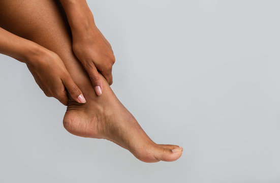 Close up of black woman massaging her ankle