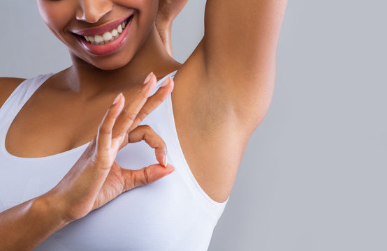 Cropped of woman looking at shaved armpit, showing okay gesture