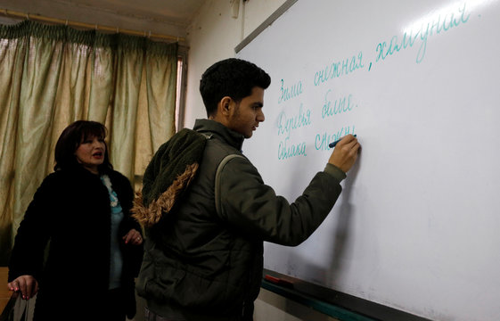A student writes in Russian on a board at a school in Damascus