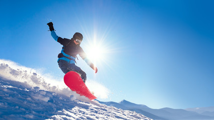 Stores à enrouleur Glisse hiver Snowboarder Riding Red Snowboard on the Slope in the Mountains in Bright Sun. Snowboarding and Winter Sports Concept