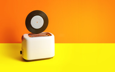 Vinyl record in a toaster on a yellow background. Creative concept of hot music, good mood in the morning.