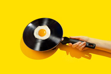 Vinyl record in a pan on a yellow background. Creative concept of a vibrant morning.