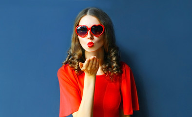 Portrait beautiful young woman blowing red lips sending sweet air kiss wearing heart shaped sunglasses on blue wall background Wall mural