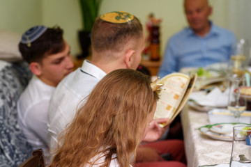 Jewish family celebrating Passover Seder reading the Haggadah. Three generations, real family.