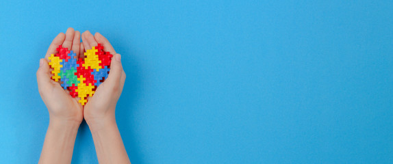 Kid hand holding colorful heart on light blue background. World autism awareness day concept