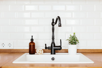 Kitchen with white sink and black faucet wooden countertop