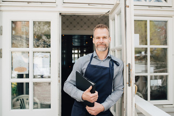 Portrait of restaurant owner standing by door